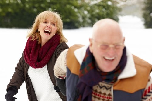 Smiling senior couple enjoying themselves in winter forest
